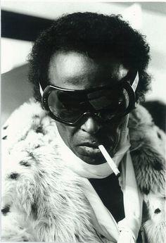 Miles Davis in fur, scarf, and superfly eyewear, ca. 1970s.