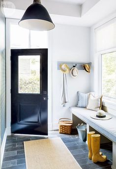 LVZ Design - A black glass front door opens to reveal a mudroom fitted with a black industrial pendant light hung from a tray ceiling over a bound sisal rug covering slate floor tiles complementing a white built in bench topped with a light gray cushion and gray pillows placed in front window covered with a white rolling shade while a gray coat rack hangs on the wall beside the door.