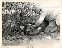 1944- U.S. medic treats a wounded German soldier during battle for Pouilly, France.