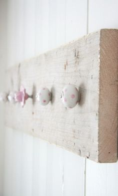 | Kapstokken | Label 123. DIY inspiration - ceramic knobs on white-washed board, for hooks in a child's room.