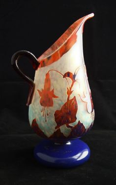 Charles Schneider Le Verre Francais Art Deco Glass Pitcher illustrated in the classic Schneider cameo colors o mettled orange shading to pure blue on a pale ground with yellow, white and plae blue suffusions. THe appliedd handle is in a contrasting clear amethyst color and the raised cameo layer is highly polished. Measures 19cm, made in France, circa 1925