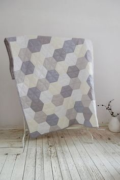 Quilt on a double bed with pastel hexagon. Modern design, soft colors perfect for the modern, simple, minimalist interiors. The bottom of the