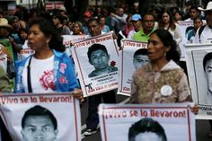 Relatives carry photos of some of the 43 missing students of the Ayotzinapa teachers' training college during a protest to mark the eleven-month anniversary of their disappearance in Mexico City, Mexico on August 26, 2015.