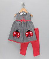 Is there anything sweeter than seersucker? We don't think so. Your tiny flower will be buzzing with ladybugs in this adorable top and leggings set. The quaint contrasting gingham prints and precious appliqués will make her picture-perfect for Grandma's house. Pair with lily white mary janes for a look that's as sweet as her giggles.Includes tunic and leggings...