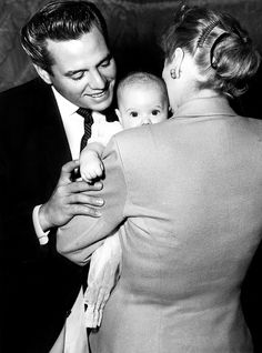 Lucille Ball and Desi Arnaz photographed with their son at his Christening, 1953