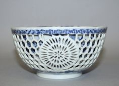 CHINESE KANGXI PERIOD BLUE & WHITE DOUBLE WALLED RETICULATED PORCELAIN BOWL, circa 1700, the outer reticulated sides with flowerheads divided by trellis, the inner sides painted with sprays of seasonal foliage, the bowl interior painted to its centre with stylised insects amidst loose floral sprays, the base with a pierced flower mark, 5.4in diameter & 2.75in high.