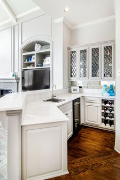 This glamorous kitchen even includes a bar area with beautiful glass front cabinets, wine storage and a mini refrigerator. A low countertop separates it from the living room while still allowing easy access when entertaining.