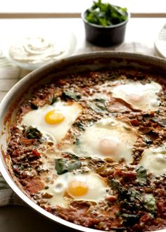 Savory baked eggs in tomatoes with lentils and spinach topped with tangy whipped goat cheese makes a low carb, vegetarian meal for any time of day.
