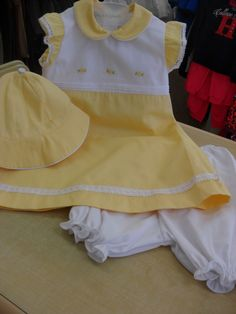 This cute set is in 100% cotton and comes in sizes 9/12,18/24 mths. the dress is in a very fine ribbed cotton and a line in shape. it has a frilled cap sleeve which is trimmed in a cotton lace ,peter pan collar edged in white across the bodice you have 3 sets of flowers and dots in yellow with green leaves beneath this are 3 rows of pin tucks on the bottom of the dress is a band of lace with ribbon slotted through and white bow on side seam.   eBay!