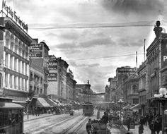 "ca. 1905)*^ - View of Broadway looking north from Sixth Street. The 7-lamp ornate streetlights that ran along the sidewalk curb consisted of a large round bulb surrounded by six smaller ones. Streetlight ""Electroliers"" are defined as free-standing streetlights generally on their own posts while ""Utilitarian"" Streetlights are lamps attached to an overhead wire or to a power pole."