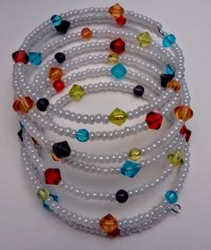 Seven coil oval memory wire bracelet, wrapping 53 inches total around your wrist. Beads: 1 millimeter white opaque luster seed beads; 2 millimeter purple, light blue, light green, gold, and red multif More