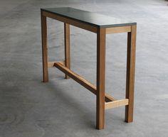 Beton-Holz-Stehtisch. Pure Wirkung von Materialien. Ohne Schnörkel. Deutsche Eiche und samtweicher Sichtbeton brauchen nicht mehr.