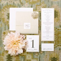 Brides.com: The Most Pin-Worthy Real Wedding Details of the Week: May 30, 2014. Stationer Jen Simpson Design used the couple's classic color palette to create these cream-and-gold invitations, programs, and table numbers. Formal script is paired with metallic details for a hint of glamor.  See more photos from Amanda and Matt's timeless Newport Beach, California wedding here.