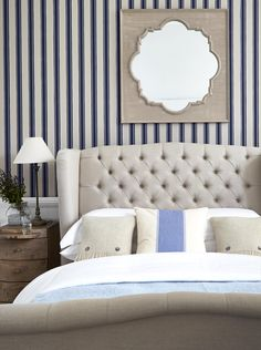 Add a subtle nautical look to your bedroom with blue and white striped wallpaper.