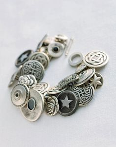 link bracelet, 40 to 60 buttons with shanks, an equal quantity of jump rings, and a pair of needle-nose pliers. For each side of each link on the bracelet: Pry one jump ring open with the pliers, then thread the ring through both the button's shank and the link itself, and use the pliers to pinch it closed again