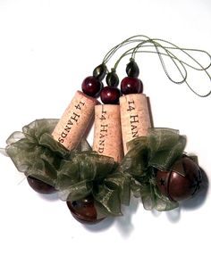 Six corkament wine cork ornaments for your holiday tree or use as gift tags. Each has a handmade bow of sheer green ribbon. Dangling at the bottom are pretty rustic look jingle bells. Each cork is saved from the land fill by being lovingly recycled and remade into something beautiful. Corkaments have many uses not limited to decorating your Christmas tree. They make wonderful additions to the top of a wrapped gift, gift bags, and bottles. Approximate dimension from top bead to bottom of...