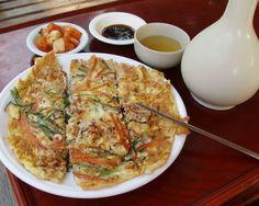 파전(pajeon) / Green Onion Pancake  A colorful pancake consisting of green onion, squid, shrimp, and oyster. It comes with a soy sauce and vinegar dip.