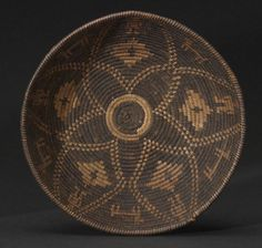 An Apache tray  Very finely woven in a negative pattern of concentric rosettes, diamonds, deer and people.  height 2 1/4in, diameter 8 3/4in