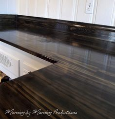 countertop makeover, really different; she used wood, 12 in. wide 1 in. thick then stained it black and varnished it....different for sure....