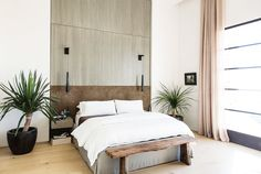 A bohemian meets modern meets minimalist bedroom with two large green potted plants and a salvaged wood bench at the end of the bed