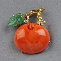 18kt Gold, Carved Emerald, and Coral Brooch, designed as a coral apple with carved emerald leaf, and diamond accents by Seaman Schepps.  Via Skinner Auctions.