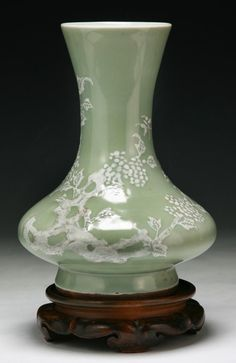 """A Chinese Antique Celadon Glazed Porcelain Vase of compressed globular form rising to a long cylindrical flared neck, presented on wood stand. Circa 1900, height: 10"""" overall"""