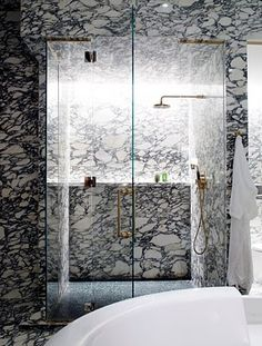Marbella | David Collins | A glamorous and elegant bathroom with exotic marble, gold brass and clean white accents. A space where bathing becomes extravagant and showering becomes a dream.