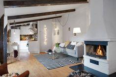 Upięta nonszalancko do belki sufitowej żarówka na kablu tworzy ciekawą nowoczesną kompozycję z pasiastym czarno-białym dywanem. Choć lampa ta ma industrialne korzenie, świetnie sprawdza się we wnętrzu z klasyczną kanapą i staroświeckim kominkiem. A razem ze świetlnym łańcuchem i lampą podłogową tworzy wyjątkowy nastrój w tym salonie.