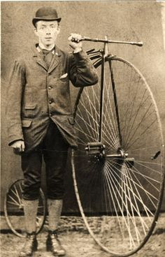 Photograph of a man, wearing a bowler hat, jacket, cravat, breeches, and boots, standing next to a penny farthing bicycle of which he is holding the handle bars; he has been identified as Mr. Turnbull