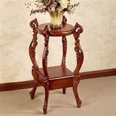 Finished in natural cherry, the Evita Accent Table lifts two wooden display shelves with its beautiful, ornate, swirling legs. Muebles Living, Craft Room Design, Corner Table, Round Tables, Side Tables, Display Shelves, Cherry, Plant Stands, Diy Ideas
