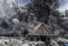 INDONESIA, Karo : Ash from Mount Sinabung volcano fills the sky over an  abandoned church during another eruption in Karo, in Indonesia's North  Sumatra province on June 19, 2015. Sinabung rumbled back to life in 2013  after a period of inactivity, since when around 10,000 people have had  to evacuate their homes. AFP PHOTO / Sutanta ADITYA