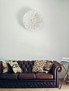 Loungeroom – above couch, a feathered Juju hat from Cameroon. Springbok skin and African hand dyed hessian cushions. Photo - Jared Fowler, production – Lucy Feagins / The Design Files. Office Interior Design, Office Interiors, Interior Decorating, Room Interior, Decorating Ideas, Black Couches, Above Couch, Brown Sofa, The Design Files