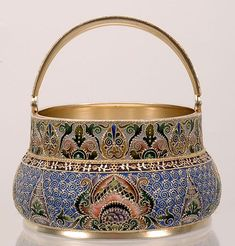 A Russian silver gilt and Pan-Slavic style shaded cloisonné enamel basket, retailed by Orest Kurlyukov, but almost certainly made by Feodor Ruckert; Moscow, circa 1908-1917. The bombe-shape basket completely covered in polychrome stylized flowerheads against a scrolling filigree and blue enamel ground beneath a wide muted enamel border of additional scroll designs, additional enamel patterns are continued on the swing arm handle.