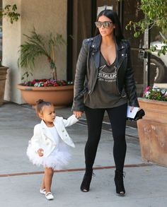 Kardashian rethinks the classic band T-shirt by looking to a style with a slouchy silhouette that shows off her ample cleavage. She tones down the sexy by wearing it with a heavy motorcycle jacket, leggings, and lace-up peep toe heels.