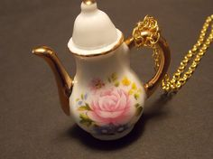 This gorgeous necklace features a 2 inch ceramic teapot painted with a large pink rose and accented in gold. The lid is securely fastened down and