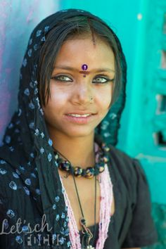 Beautiful green-eyed Rajasthani girl wearing a head-scarf and traditional make-up (India)