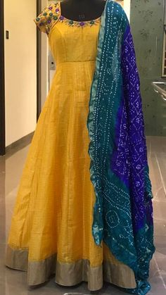 Stunning sunshine yellow color floor length anarkali dress with royal blue color bandini dupatta. Anarkali dress with floret lata design hand embroidery work on neckline. Half Saree Designs, Sari Blouse Designs, Dress Neck Designs, Bridal Blouse Designs, Indian Long Dress, Indian Gowns Dresses, Bandhani Dress, Kalamkari Dresses, Long Gown Dress