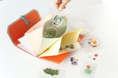 切手やボタン、リボンに押し花といったこまごまとしたマテリアルは、透明の小袋(OPP袋)に入れてから封筒で仕分ければ、中身がひと目でわかるうえ、グループごとにまとめて取り出せて便利。/手作り文房具(「はんど&はあと」2013年8月号)