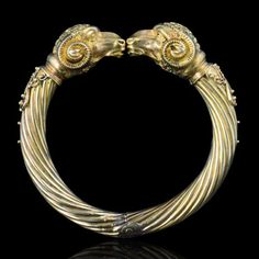 Victorian and Etruscan style  Gold rams Head Bangle c.1870    Ribbed twisted gold bangle terminating in two textured gold ram's heads, topped by pierced scrolled gold, with scrolled ribbed horns, flanked by scrolled wire tipped by small polished gold balls.  English Setting18ct yellow gold