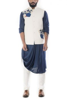 Featuring a royal blue cowl drapped kurta with a light cream nehru jacket and a white churidar. The jacket has beautiful floral embroidery on its yoke. Fabric specification: The kurta is made of cott. Mens Indian Wear, Mens Ethnic Wear, Indian Groom Wear, Indian Men Fashion, Mens Wedding Wear Indian, Wedding Dress Men, Indian Wedding Outfits, Indian Outfits, Indian Weddings