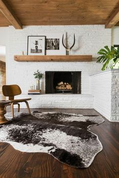 White brick fireplace with all wood ceilings mixed with mid century modern furniture and cowhide rug.