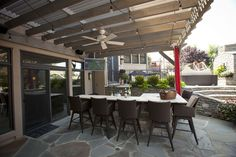 Attached timber frame pergola with louvered roof, outdoor TV, fan, kitchen and curtains.