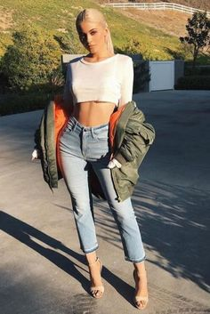 Kylie Jenner wearing Naked Wardrobe Sheer De La Crop Top, Vetements Oversized Bomber Jacket, Good American Good Cuts Raw Released Hem Jeans in Blue016 and Gianvito Rossi Suede Simple Sandals