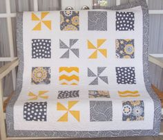 Baby quilt in yellows, grays, and cream square and pinwheel block. via Etsy