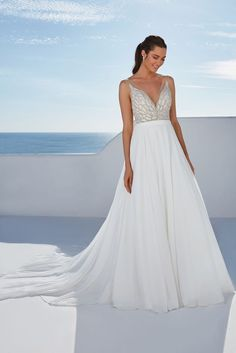 A beaded beauty! This beaded illusion bodice features a deep V-neckline and is paired with a circular cut chiffon skirt. The chapel length train finishes off this ethereal look.This style is available with two different raised neckline options for a more modest look. For a bride that's loving this gown but wanting a slimmer fit, this style is also available in a version with a crepe fit and flare skirt.