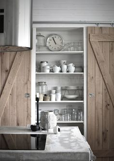 Wooden sliding doorson the wall cabinets in the kitchen with a doorway between the cabinets