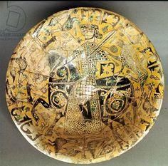 Iran, A Nishapur Glazed bowl depicting a warrior on horseback surrounded by animals and birds, 9th century . کاسه سرامیکی منقوش لعاب دار با شمایل مردی سوار بر اسب و حیوانات در اطراف با نوشتاری در حاشیه، نیشاپور، قرن ۹ میلادی by: Virtual Museum of Iran Art page on facebook.