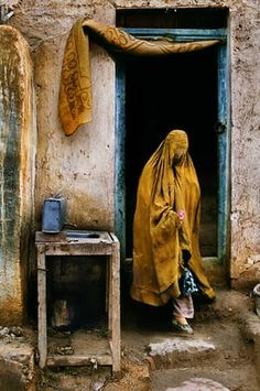 Faryab province, 1992: A widow reduced to begging comes out of a restaurant having just received money from a patron