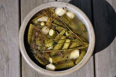 Pack your cukes tightly into a crock or a mason jar, along with whole garlic cloves, lots and lots of whole peppercorns, and whole dill stal...