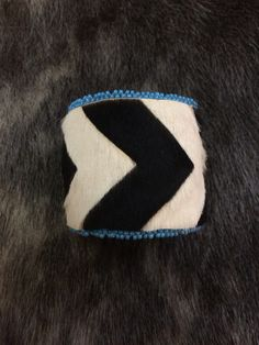 Black and white calfskin cuff bracelet with blue beads made by Bobby Itta (Inupiaq).